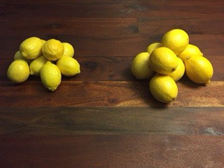 Pile of organic lemons next to a pile of conventional lemons.