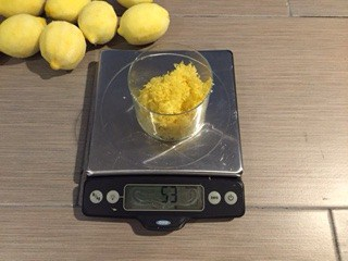 Glass of lemon zest on a food scale.